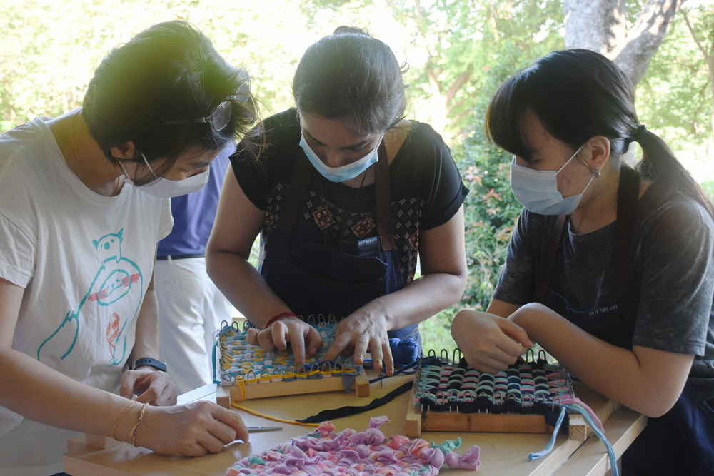Smiha (centre) is helping Zhuang (left) to overcome some difficulties in her weaving. (Photo by Wong Siew Kuen)